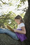 Girl reading book in tree Stock Photos