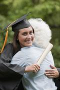 Stock Photo of Graduate hugs elderly woman