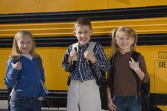 Children with back packs in front of school bus - stock photo