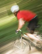 Blurred shot of man riding mountain bike - stock photo