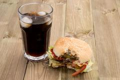 bitten off burger with softdrink - stock photo