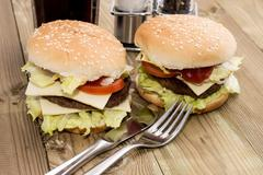 Two cheeseburger on wooden background Stock Photos