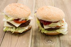 two cheeseburger on wooden background - stock photo