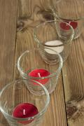 Glasses with candels on wood Stock Photos
