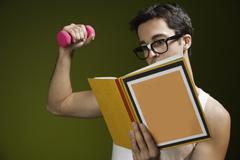 Nerdy man lifting weight and reading book Stock Photos