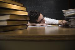 Nerdy man sleeping on school desk - stock photo