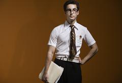 Nerdy man holding school books - stock photo