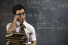 Nerdy man in front of blackboard - stock photo