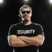 Security guard with headset posing with arms crossed Stock Photos