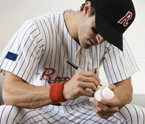 Close up of baseball player autographing baseball - stock photo