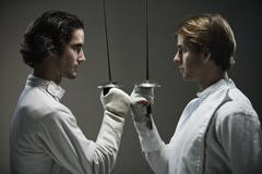 Fencers facing off with fencing foils Stock Photos