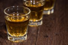Stock Photo of line of rum shots on wooden background