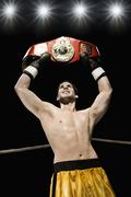 Boxer holding championship belt overhead in boxing ring Stock Photos