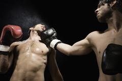 Boxer punching opponent in jaw Stock Photos