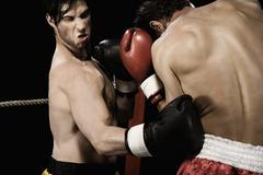 Boxers fighting in boxing ring Stock Photos