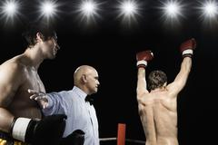 Referee holding losing boxer back from winner Stock Photos