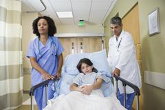 Tyttö on työntämisestä sairaalassa Gurney Kuvituskuvat