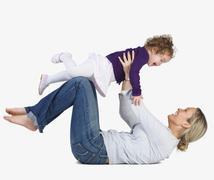 Mother lifting daughter into air Stock Photos