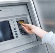 Stock Photo of Woman using cash machine