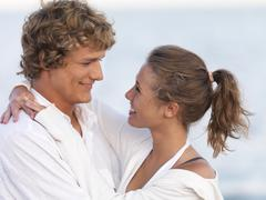 Young couple hugging on beach - stock photo