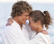 Young couple hugging on beach Stock Photos