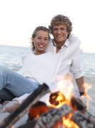Young couple hugging by campfire on beach - stock photo