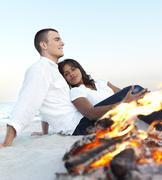 Young couple relaxing by campfire on beach - stock photo