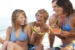 Young couples eating watermelon on beach Stock Photos