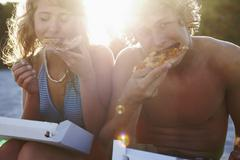 Young couple eating pizza on beach Stock Photos