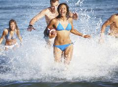 Young friends playing football in ocean Stock Photos