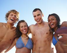 Young couples laughing on beach - stock photo