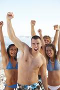 Young friends raising arms on beach Stock Photos
