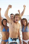 Stock Photo of Young friends raising arms on beach