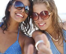 Portrait of young women posing on beach Stock Photos