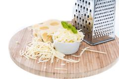 Emmentaler with cheese grater on white Stock Photos