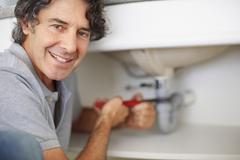 Fixing a leaky sink - stock photo