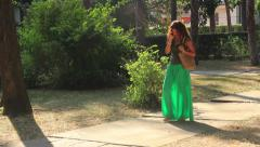 Pretty young woman with green drees walking in the park and talking on mobile. Stock Footage