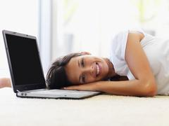 Woman resting beside laptop Stock Photos