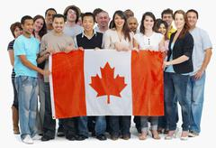 Group of people holding Canadian flag - stock photo
