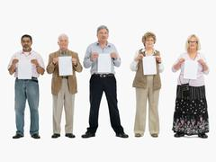 Group of people standing in a row holding papers - stock photo
