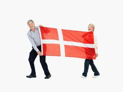 Two people carry the Danish flag - stock photo
