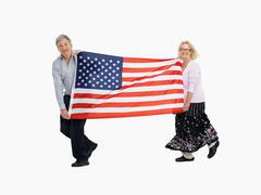 Two people carrying the American flag - stock photo
