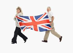 Two people carrying the British flag - stock photo