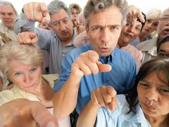 A group of people pointing their fingers in accusation - stock photo