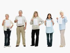 Group of people standing in a row holding papers Stock Photos