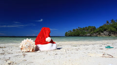 Santa claus hat and sea shell on beach Stock Footage