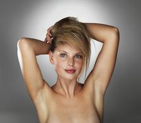 Seductive blond woman with her hands behind her head - stock photo
