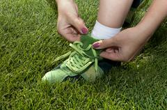 woman ties laces on green shoes - stock photo