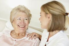 Nurse sitting with a senior woman Stock Photos