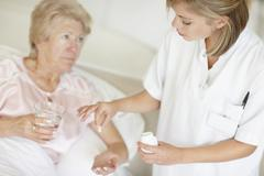 Nurse giving pill to senior woman Stock Photos